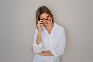 Woman Smiling And Holding Glasses