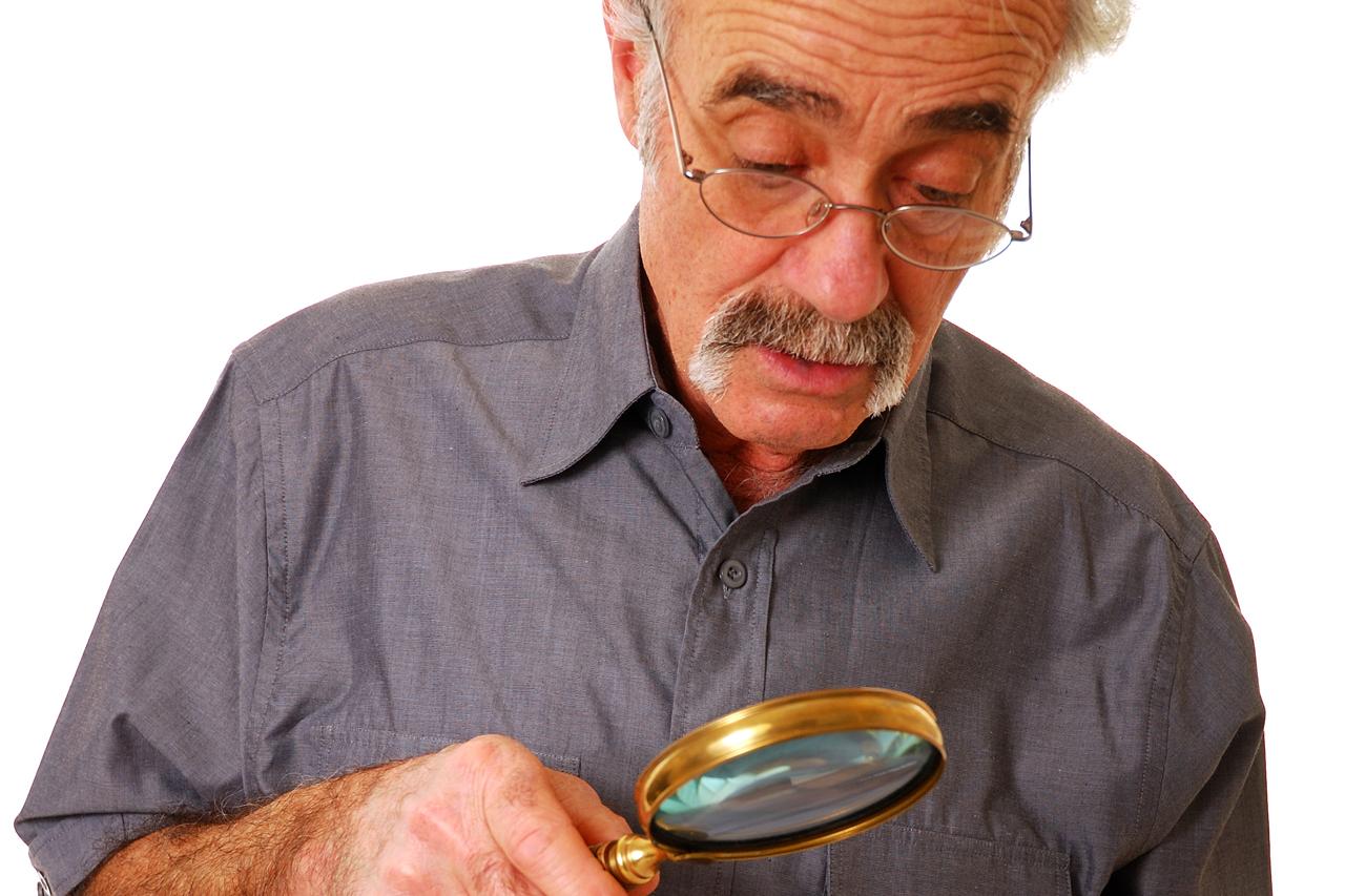 Man wearing eyeglasses, using magnifying glass