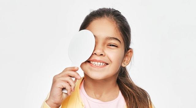 Mixed Race Female Kid Having Eye Exam With One Eye Covering Usin