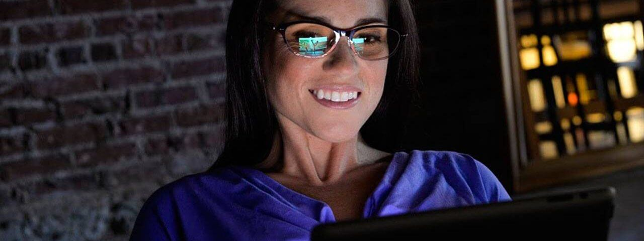 Woman wearing computer glasses while on tablet