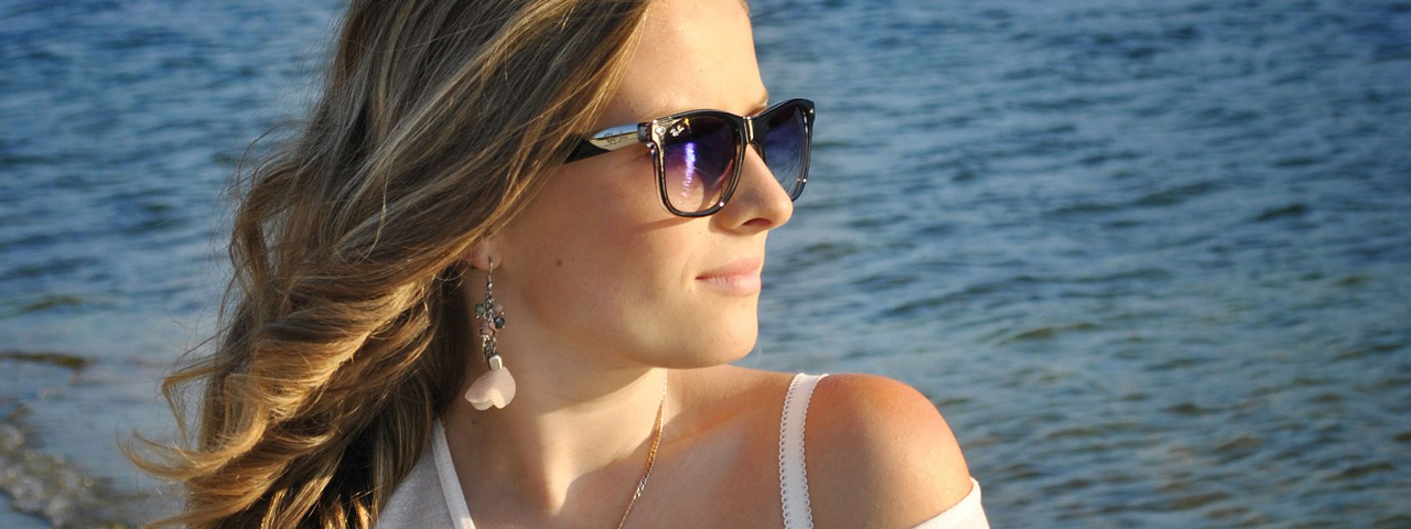 Woman on a beach wearing sun glasses, Eye Care in Colorado Springs, CO