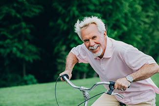 Lively Older Man Riding His Bicycle, Laughs And Enjoys Life. Sen