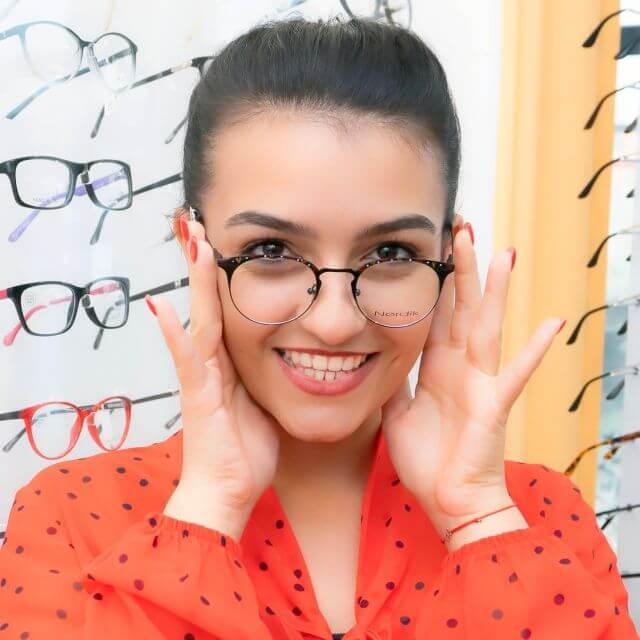 woman smiling trying on glasses