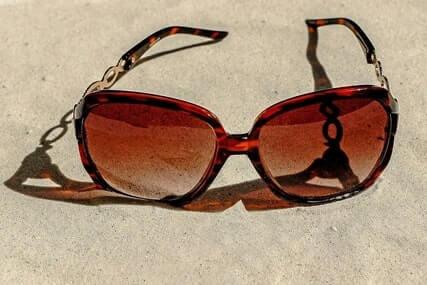 pair of sunglasses on sand
