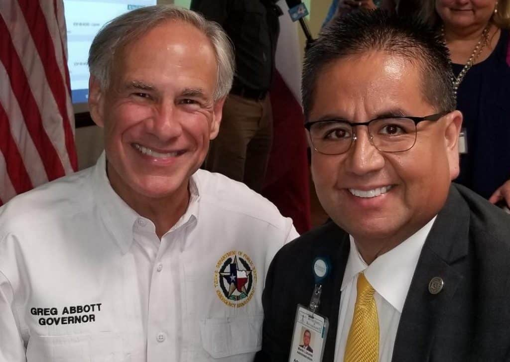Featured: Gov. Greg Abbott and Mario Lizcano, Administrator of Community Engagement and Corporate Affairs for DHR Health, pose for a photographer during a visit to the Rio Grande Valley by the governor for the emergency management meeting during the summer of 2018 in Edinburg in the conference room of the Hidalgo County Health Department.  Photograph Courtesy MARIO LIZCANO