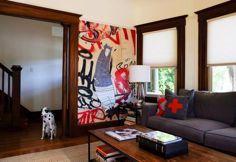 An Arts & Crafts living room in Alameda, California features a mural based on a piece of street art originally captured in Brooklyn