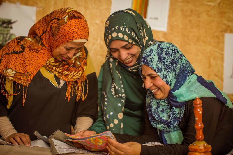 Syrian refugee artisans reviewing a new design.