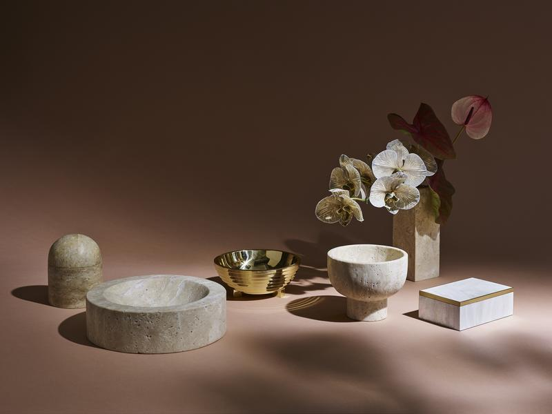 The collection comprises marble, brass, travertine, pen shell and stone