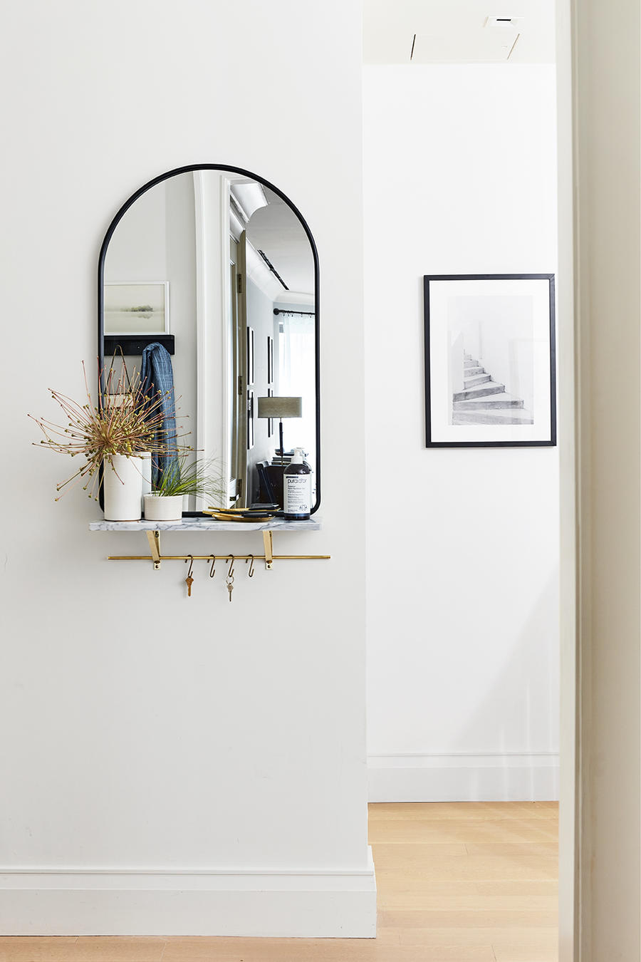 In the era of COVID, the entryway in the Real Simple House a bottle of hand sanitizer perched under the mirror.