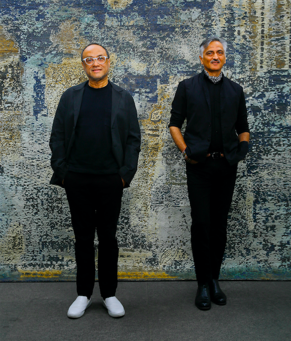 Designers David Abraham and Rakesh Thakore in front of the Sanganer carpet, inspired by the patterns on the borders of saris.