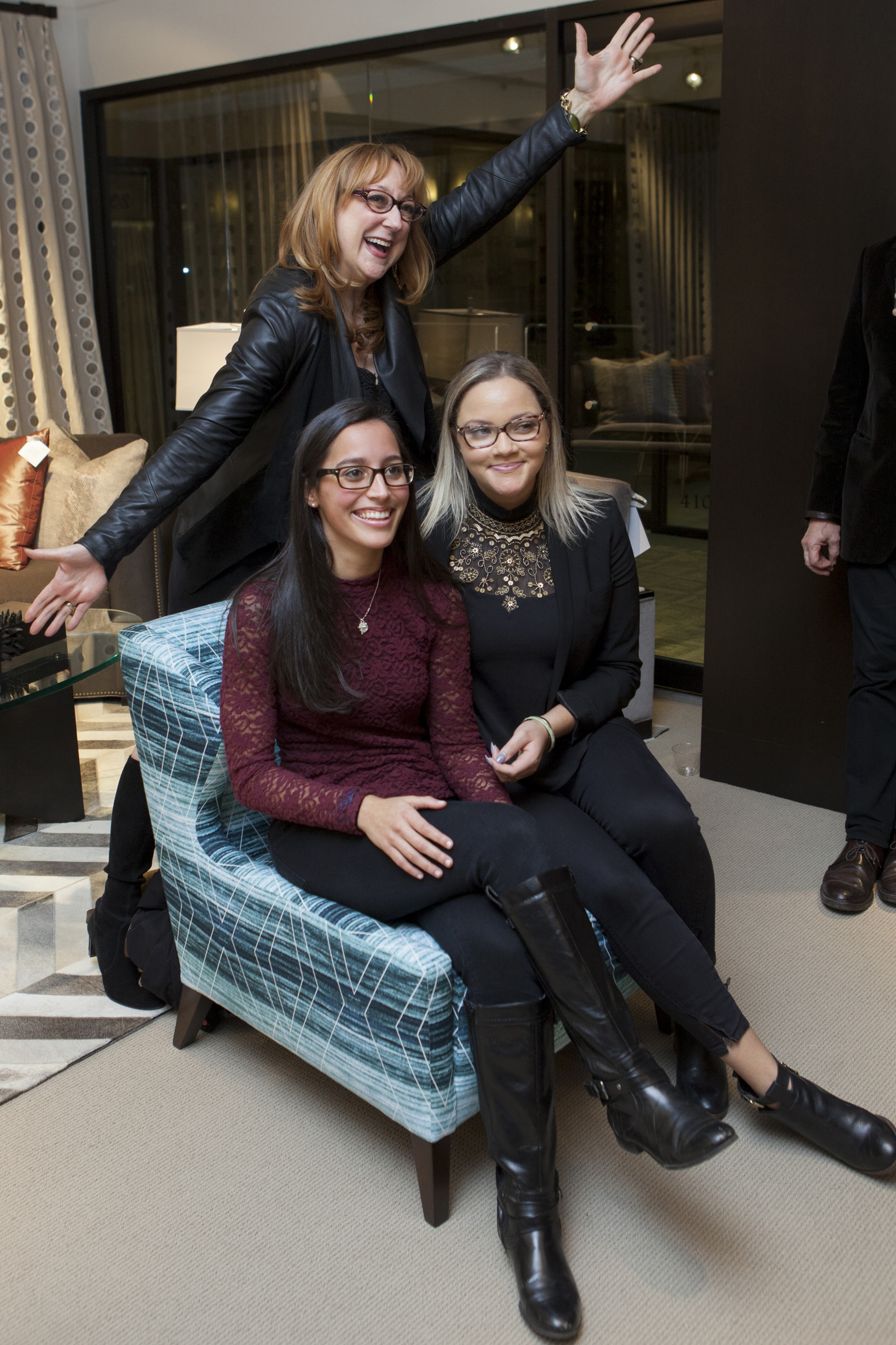 Two members of the winning team, NYIT students Victoria Rouse and Destiny Bates, pose with their mentor, Robin Baron, on the chair upholstered in the fabric they designed. (Not pictured: team member John Sanchez)