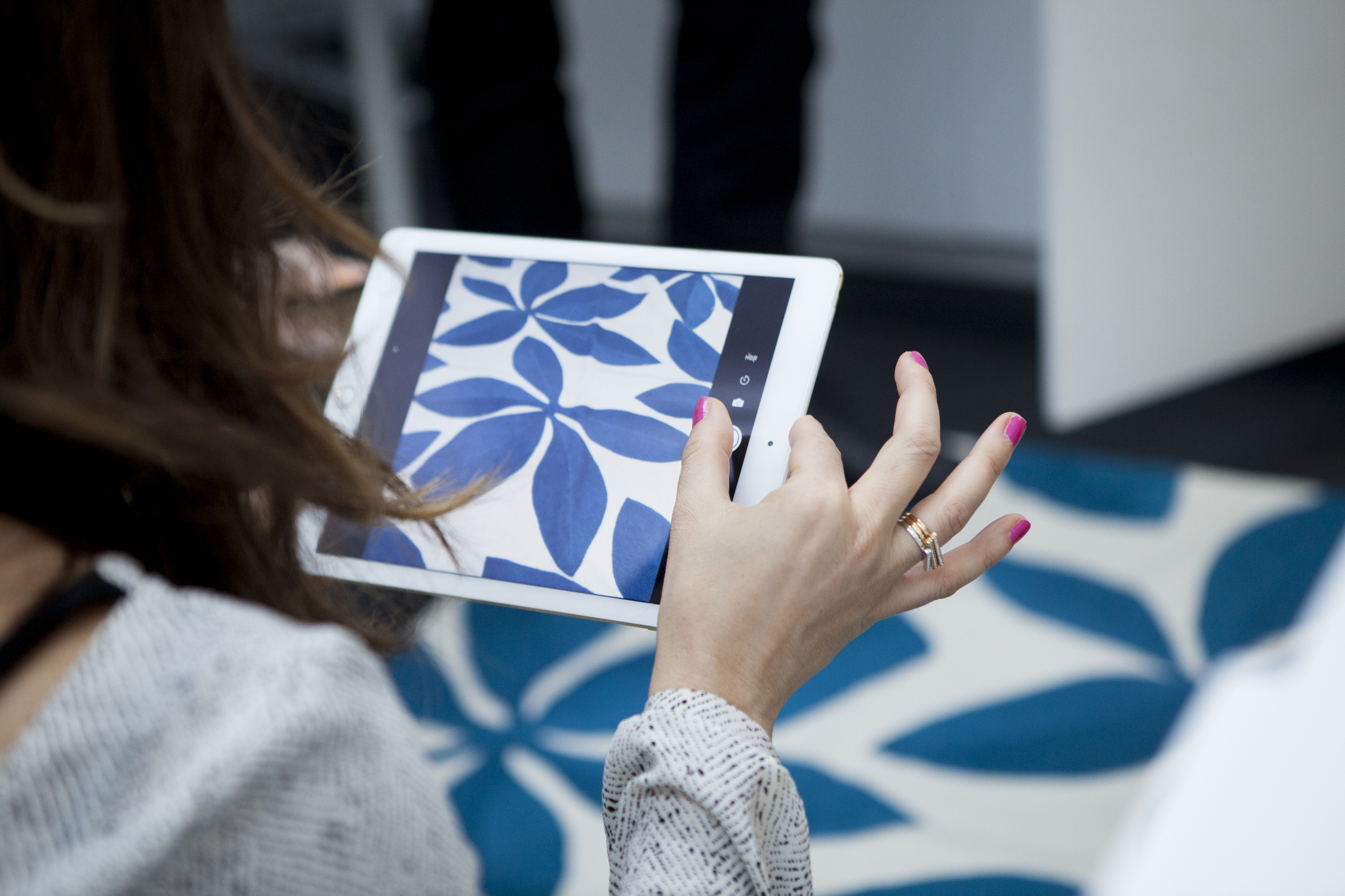 A student takes a shot of one of Judy's vibrant hand-knotted rugs.