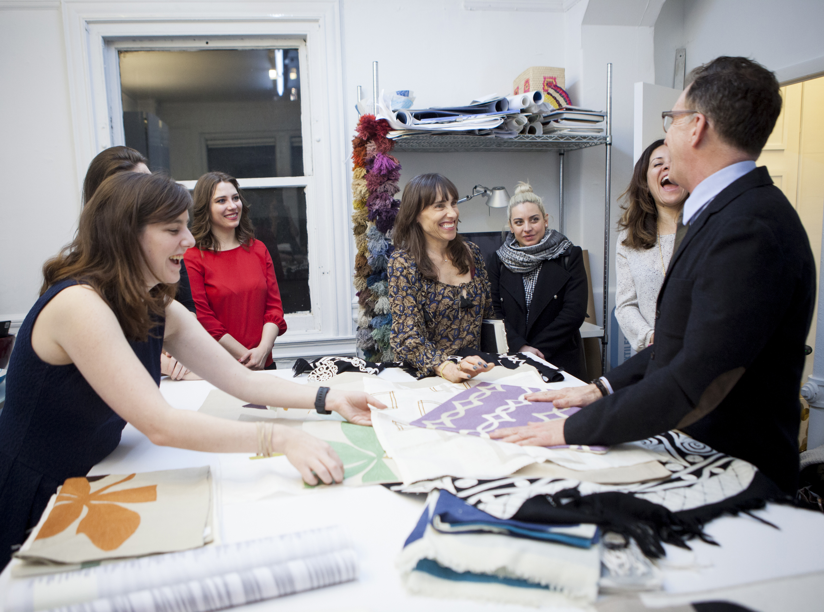 The group sharing laughs and looking at handwoven pillows