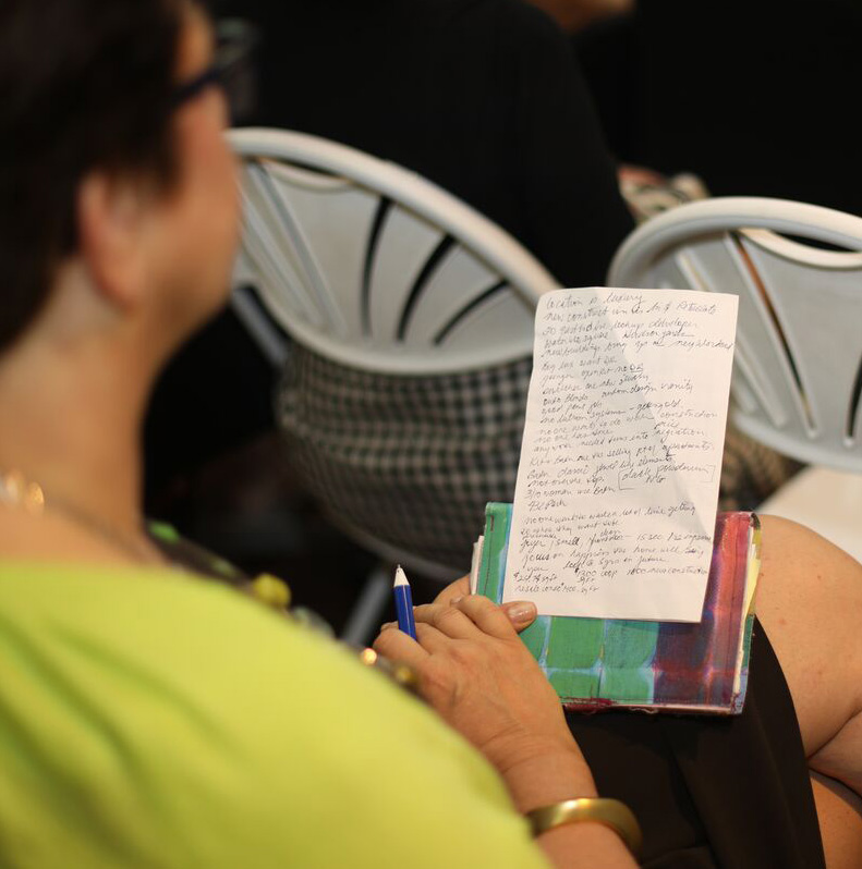 An attendee takes notes during the discussion