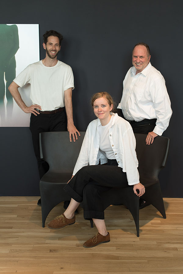 Parsons students Gregory Benson and Sarah Burns pose with Bruce Bierman on Patrick Naggar's seating.