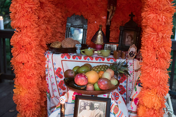 The altars are decorated with candles, buckets of flowers (wild marigolds called cempasuchil and  bright red rooster's combs) mounds of fruit, peanuts, plates of turkey mole, stacks of tortillas and big Day of the Dead breads called pan demuerto. The altar needs to have lots of food, bottles of soda, hot cocoa and water for the weary spirits.