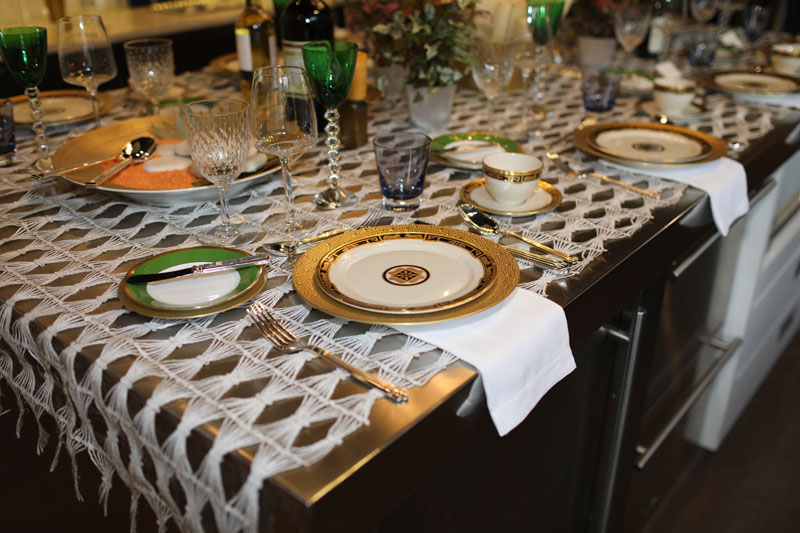 Tablescape created by Asler Valero, featuring a mix of brands from Replacements Ltd., including Bernardaud, Christofle and Baccarat, in shades of bold greens, majestic blues and pops of gold