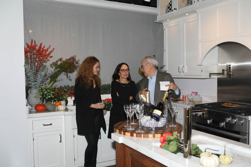 Regina Bilotta and her husband, Eric Witkin, chat with Jennifer Flanders (left) in the kitchen she styled.