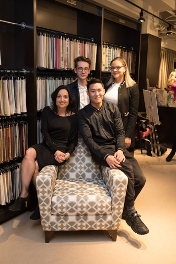 The winning team: students Destiny Bates of NYIT, Connor Lucas of Parsons, Paul Lee of NYSID, and their mentor, Jan Jernoske of Transitional Interiors posing with their winning design upholstered on the Kravet armchair