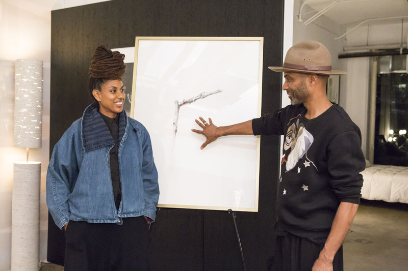 Anishka Clarke and Niya Bascom  looking at a piece of art by Jinseikou