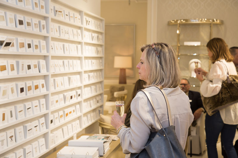 """Caracole customer browsing the """"Off the Wall"""" cards in the showroom"""