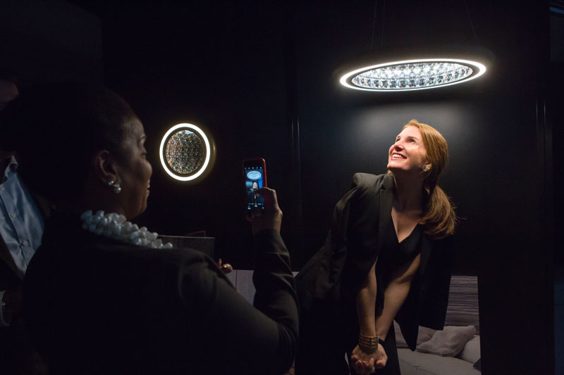 Joy Moyler snapping Sophie Donelson posing under Swarovski Lighting's Infinite Aura collection