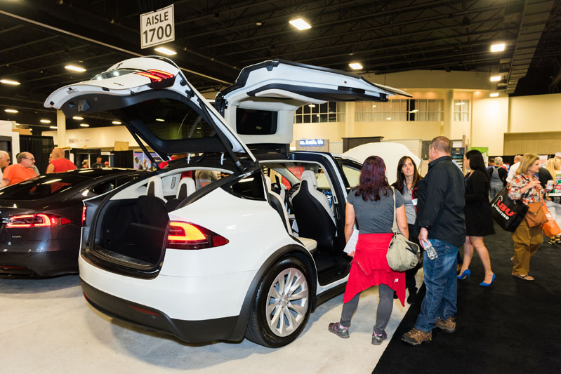 Attendees marvel at Tesla's display.