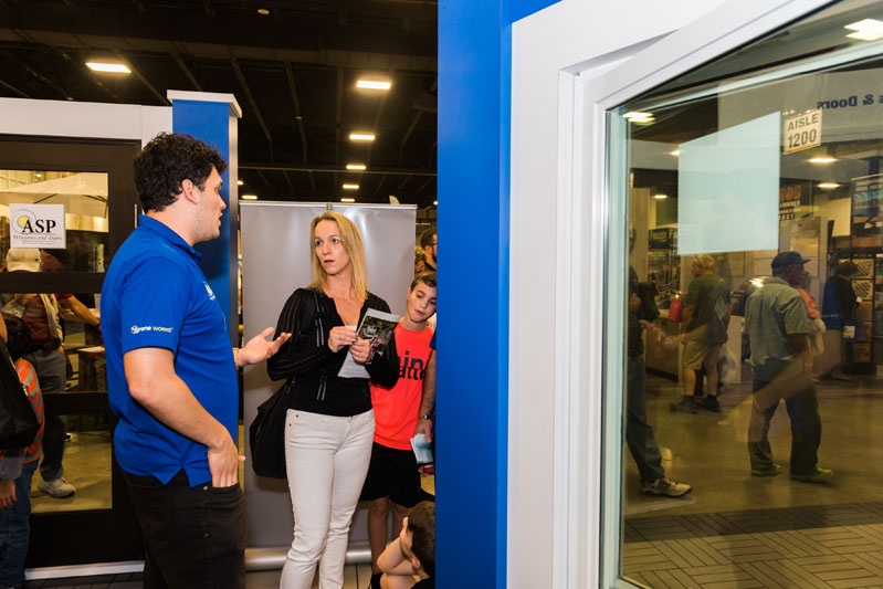 An exhibitor and attendee discuss windows.