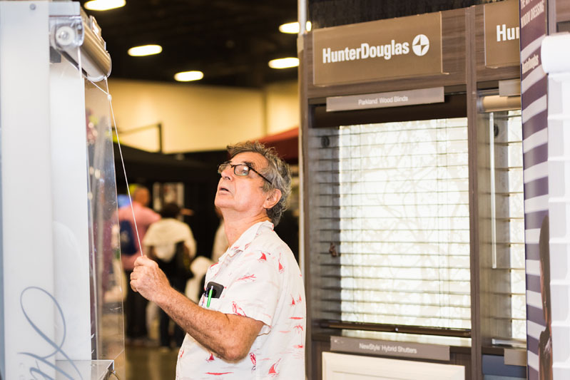 An attendee gets hands-on with a Hunter Douglas display.