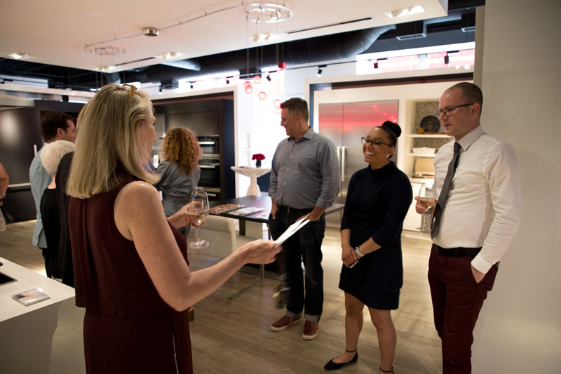 Monique Robinson (second from right) gives guests an overview of new appliances.