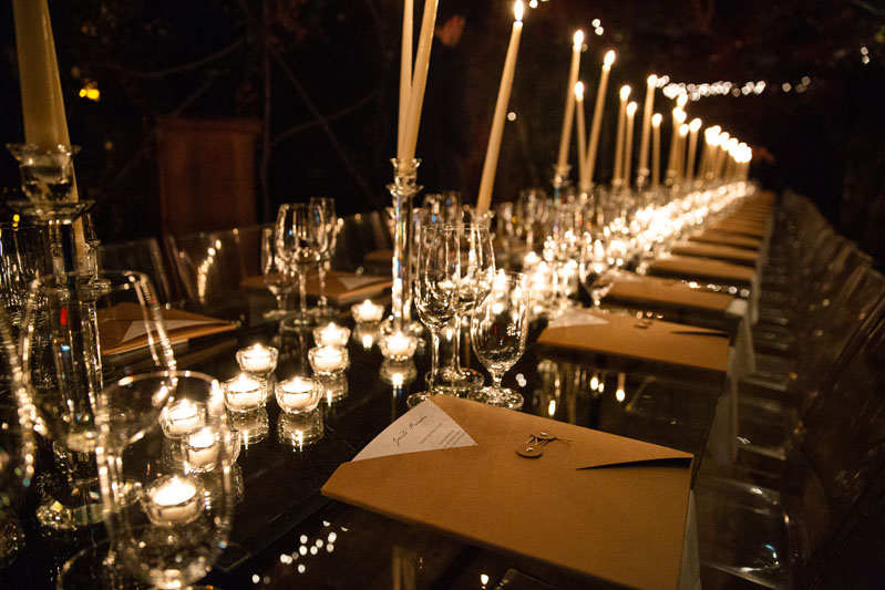 Guests dined at long, candle-lit tables.