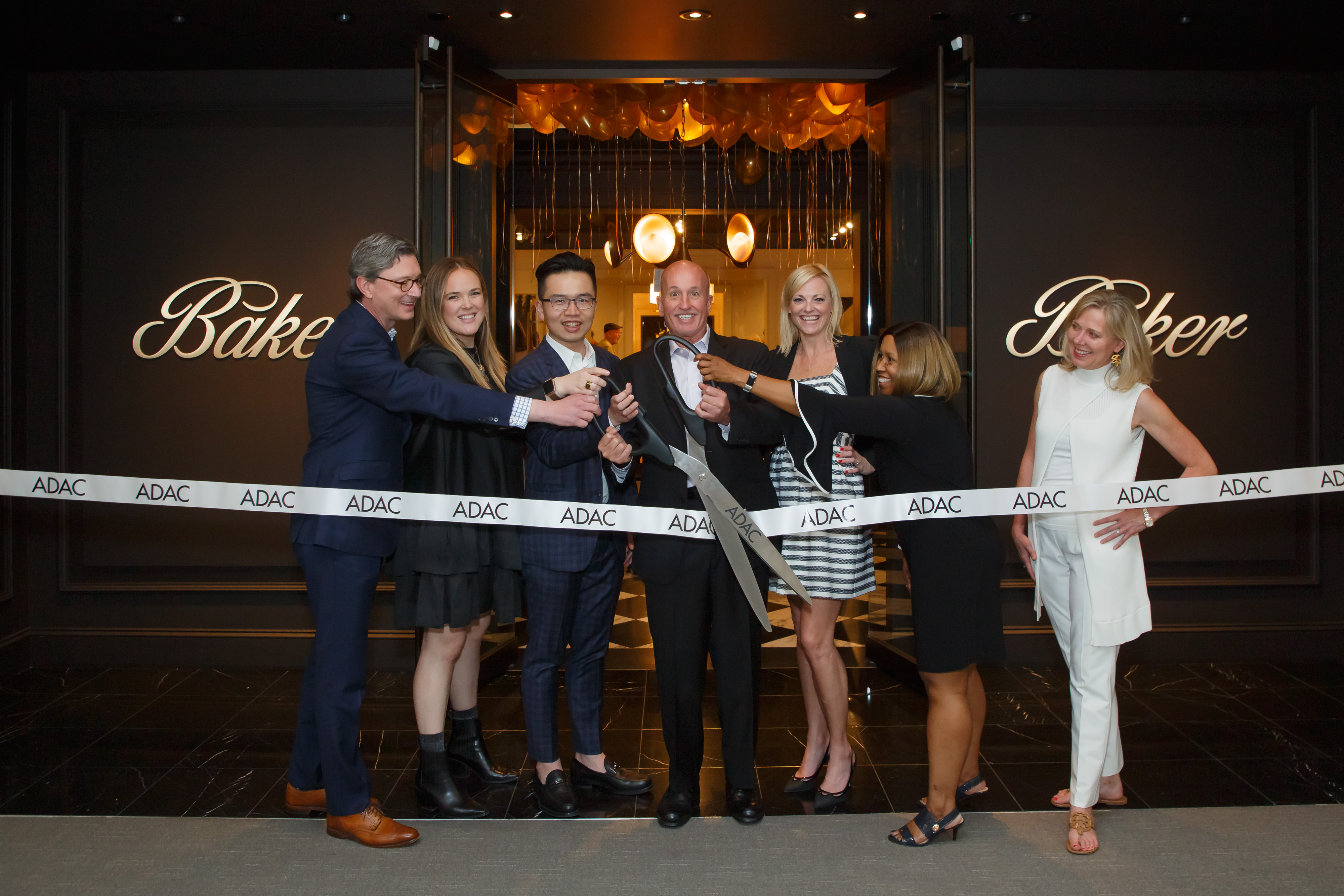 The ribbon cutting at Baker's grand-opening party with the Baker team, Katie Miner and Kim Johnson