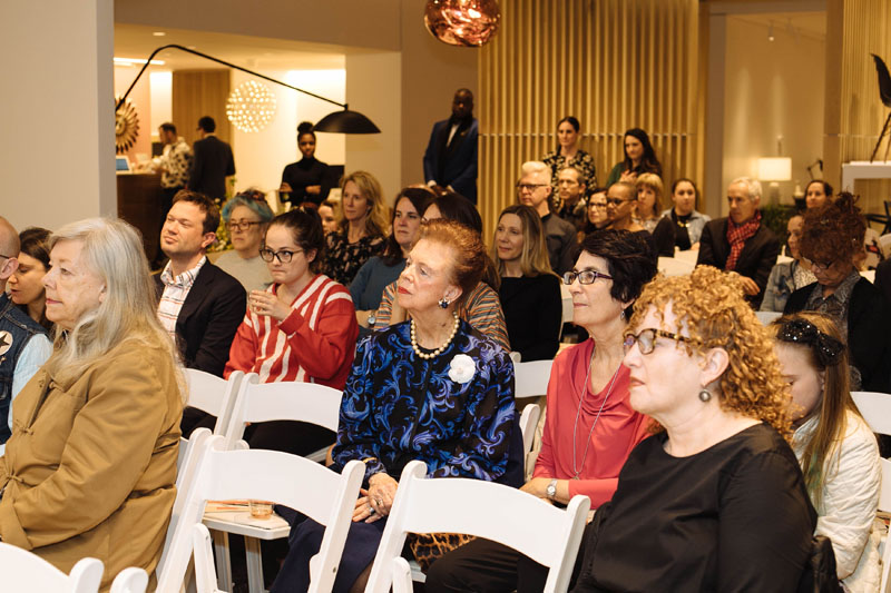An enraptured crowd listens to the conversation.