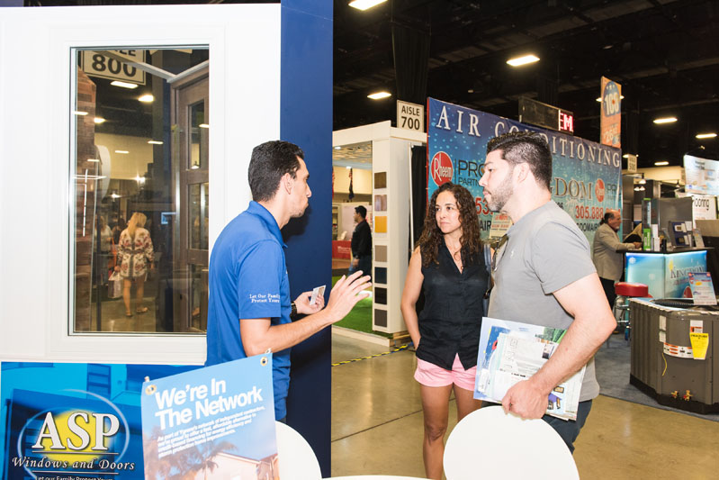 Guests visit the ASP Windows and Doors booth.