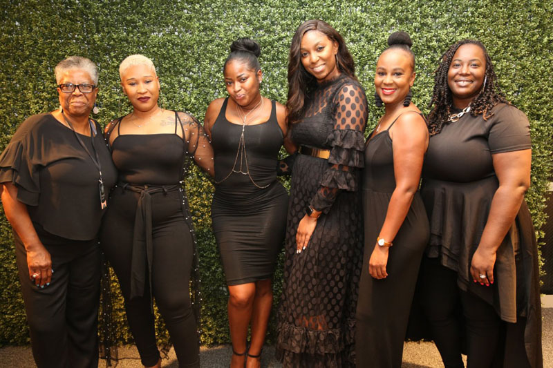 Attendees of the All Black Vignette Party pose for a photo.