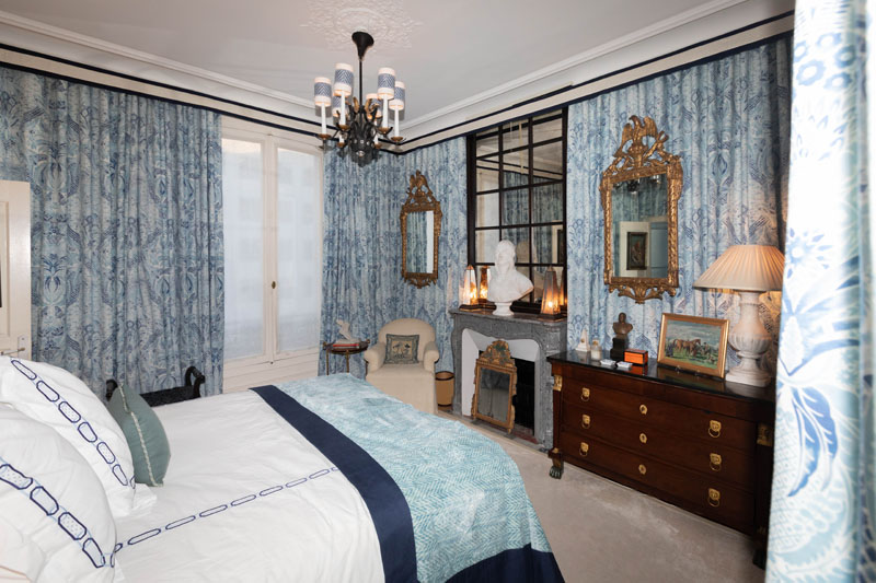 Timothy Corrigan's master bedroom features wall-to-wall blue damask drapery.