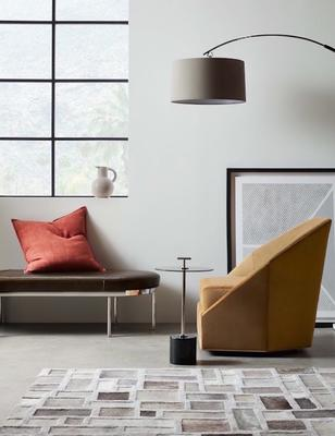 The Colburn Leather Cocktail Ottoman with the Jewel Full Swivel Chair, Handled Pull-up Table and Ari Floor Lamp