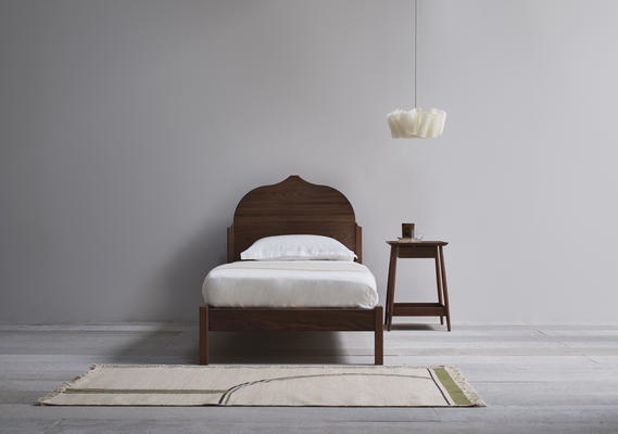 The upholstered headboard and frame follows the design's sculptural lines.