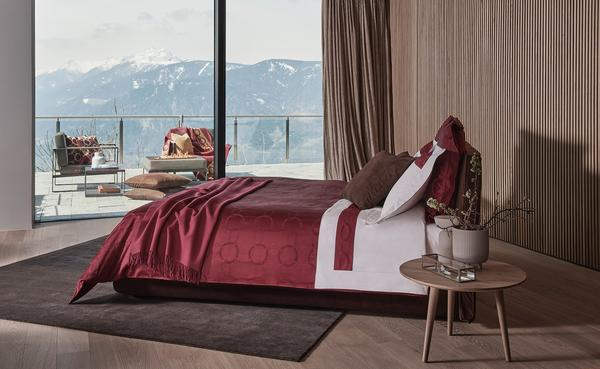 Chains duvet cover in Amaryllis paired with Chains Border sheet set in White-Amaryllis, Pure Cashmere throw in Amaryllis and Luxury Suede decorative pillows in Dark Brown.