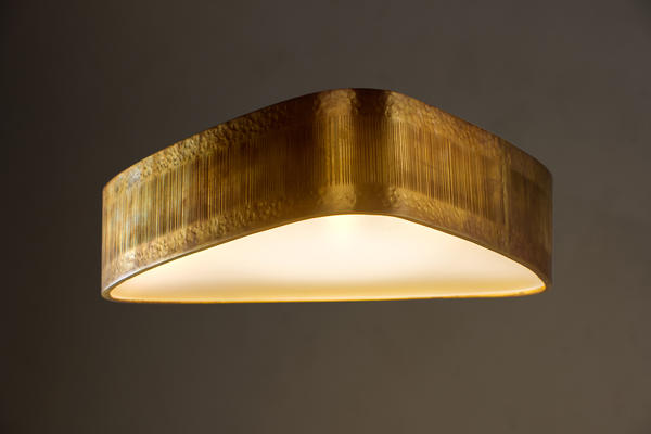 The soft triangular shape of the Allegra Bulkhead creates a unique ceiling light. Made out of solid brass and with a textured surface pattern, the Allegra Bulkhead epitomises the organic feel of the collection.