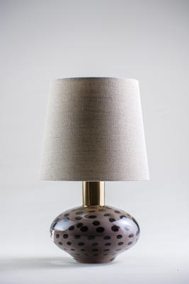 Small, attention-grabbing and cute, the Auden lamp is formed of blown glass and patinated brass. Each Auden lamp has its own character, formed by the artistry of the glass blowing technique. The lamp's dotted surface is both playful and decorative, resembling the paintings of Yayoi Kusama.