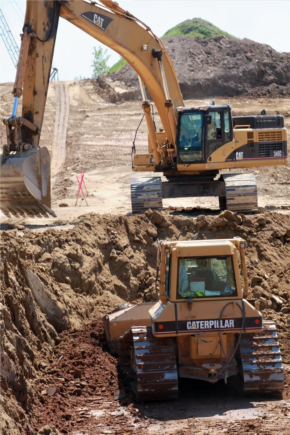 A Cat excavator and dozer work in tandem to remove fill where a portion of the new road bed was lowered up to 12 ft. (3.7 m).