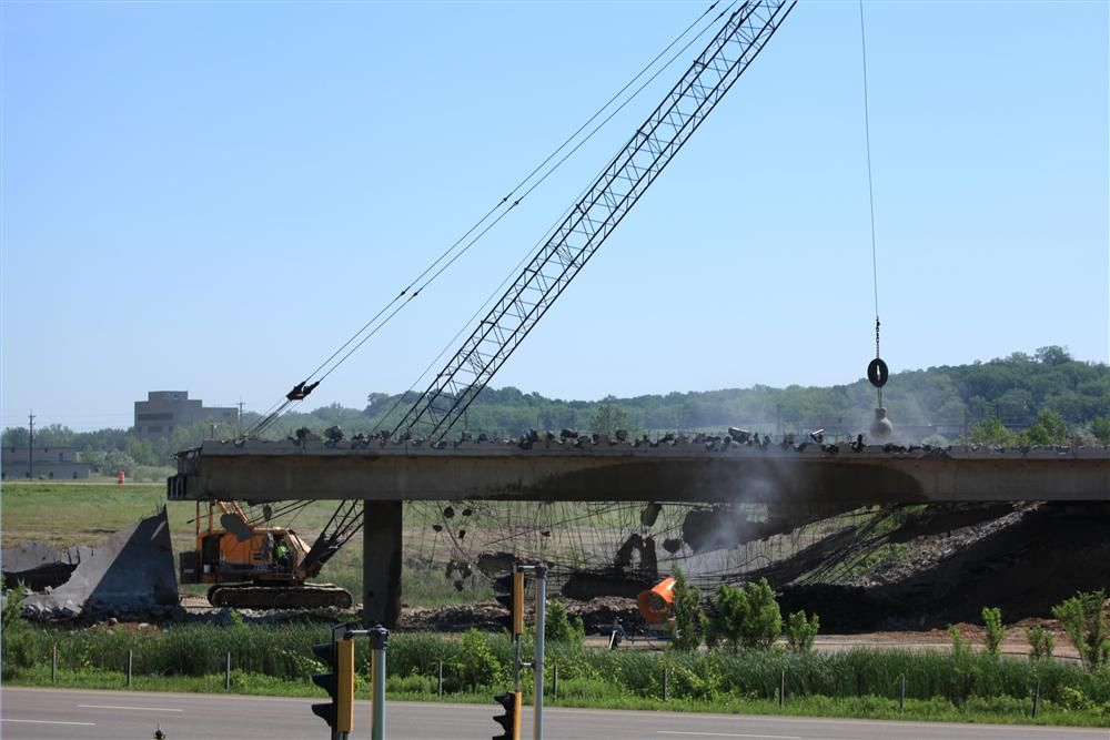 The operator of an American crane swings a wrecking ball to bring down one of a pair of bridges carrying TH-10 traffic over I-35W.