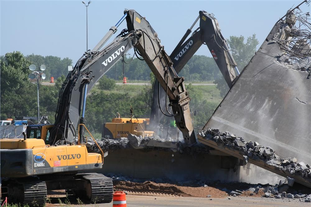 Volvo excavators break up concrete on a bridge that was removed and reconstructed on the western edge of the project. The bridge is part of a pair of bridges bringing TH-10 over I-35W. They were removed over a weekend closure of I-35W carrying thousands o