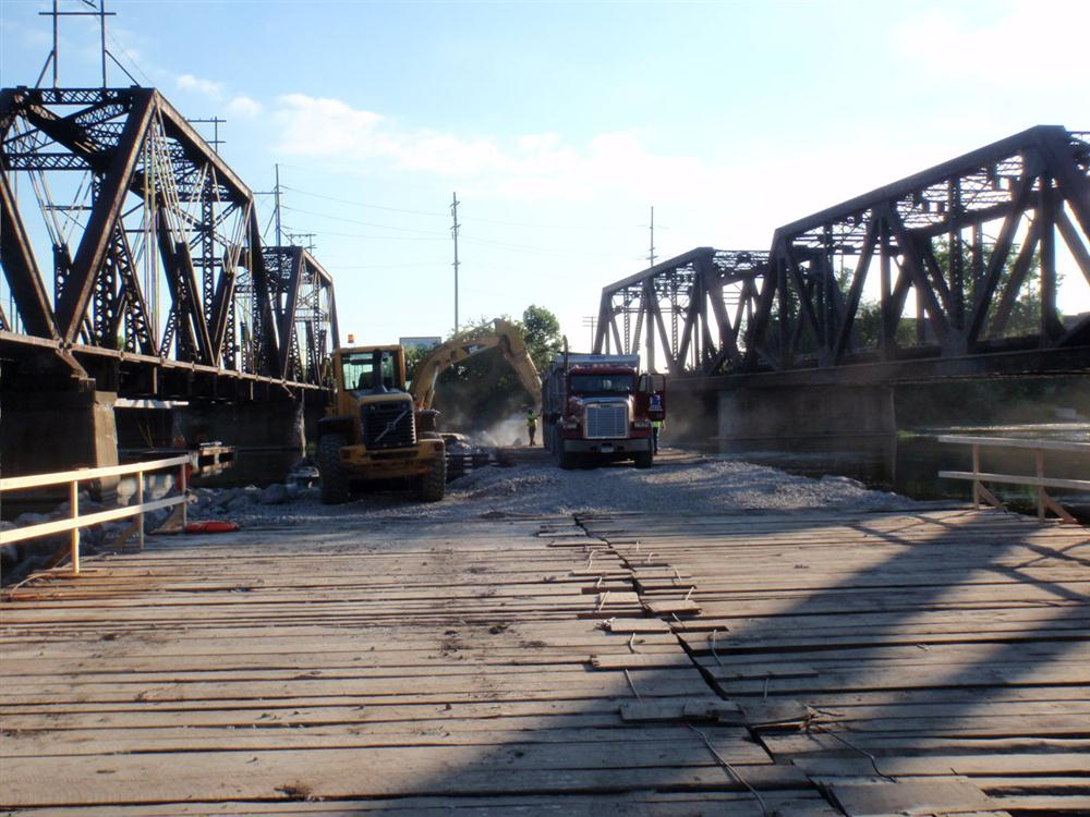 The existing bridge is being maintained while crews will build a new substructure (with reinforced concrete) beneath it. A new superstructure with a metal deck shall be built in a nearby laydown yard.