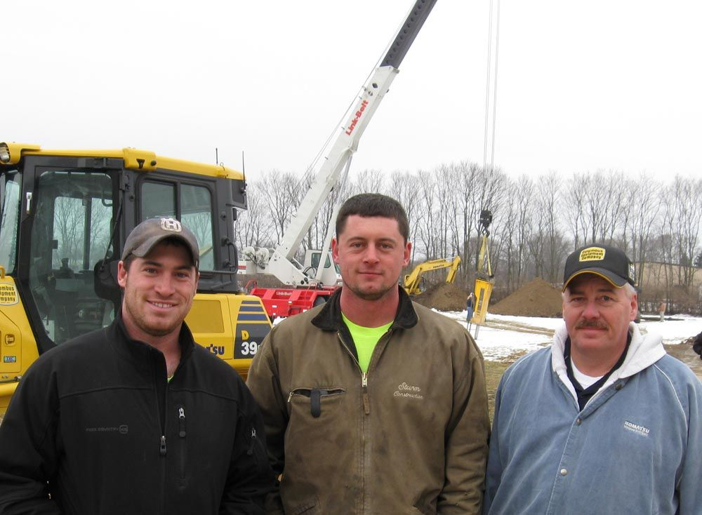 (L-R):  Adam and Andy Sturm of Sturm Construction talk with Mike Montgomery, Columbus Equipment Co. technical trainer, about the new PC200LC-8 hybrid excavator. After putting the excavator through its paces, Adam was impressed with the cycle times and  wi