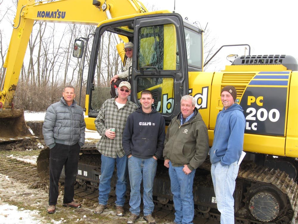 (L-R): Columbus Equipment's Mike Early gives an overview of the PC200LC-8 hybrid excavator's features to Mike Schwieterman (in cab) of Cy Schwieterman Inc., Mike Howard, and Sommer Excavating's Travis Russell, Andy Sommer, and Zach Wilde