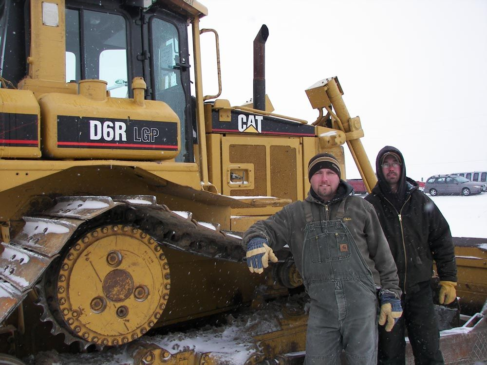 Chris Nickol (L) of Tschiggfrie Excavating in Dubuque, Iowa, and Jake Lehman of 4J Fence Co. in New Vienna, Iowa, check out the many dozers like this Cat D6 as well as a sheepsfoot if it is the right price.