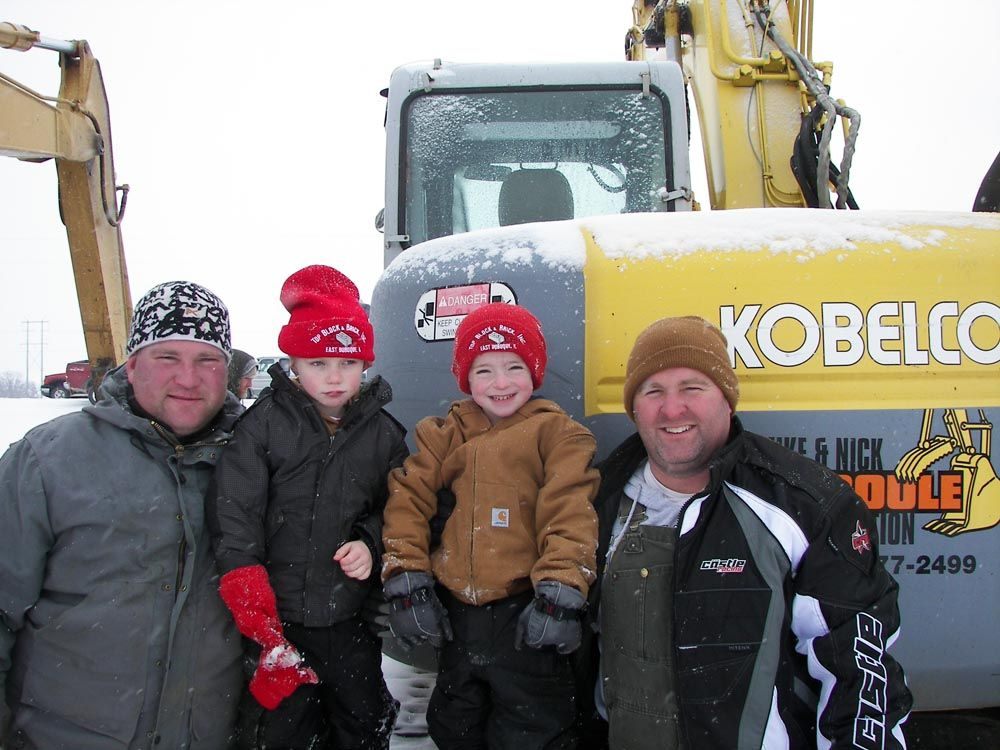 (L-R): Dustin Duggan and his son Luke of Bellair Construction join Brice and Dan Petitgout of Top Block & Brick to check out all of the machines for sale, including this Kobelco 135SR.
