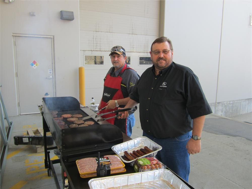 Gary Sofia (L), shop foreman, and Mike Moore, hauling coordinator, Murphy Tractor & Equipment Co. Inc., help grill the food for the event.